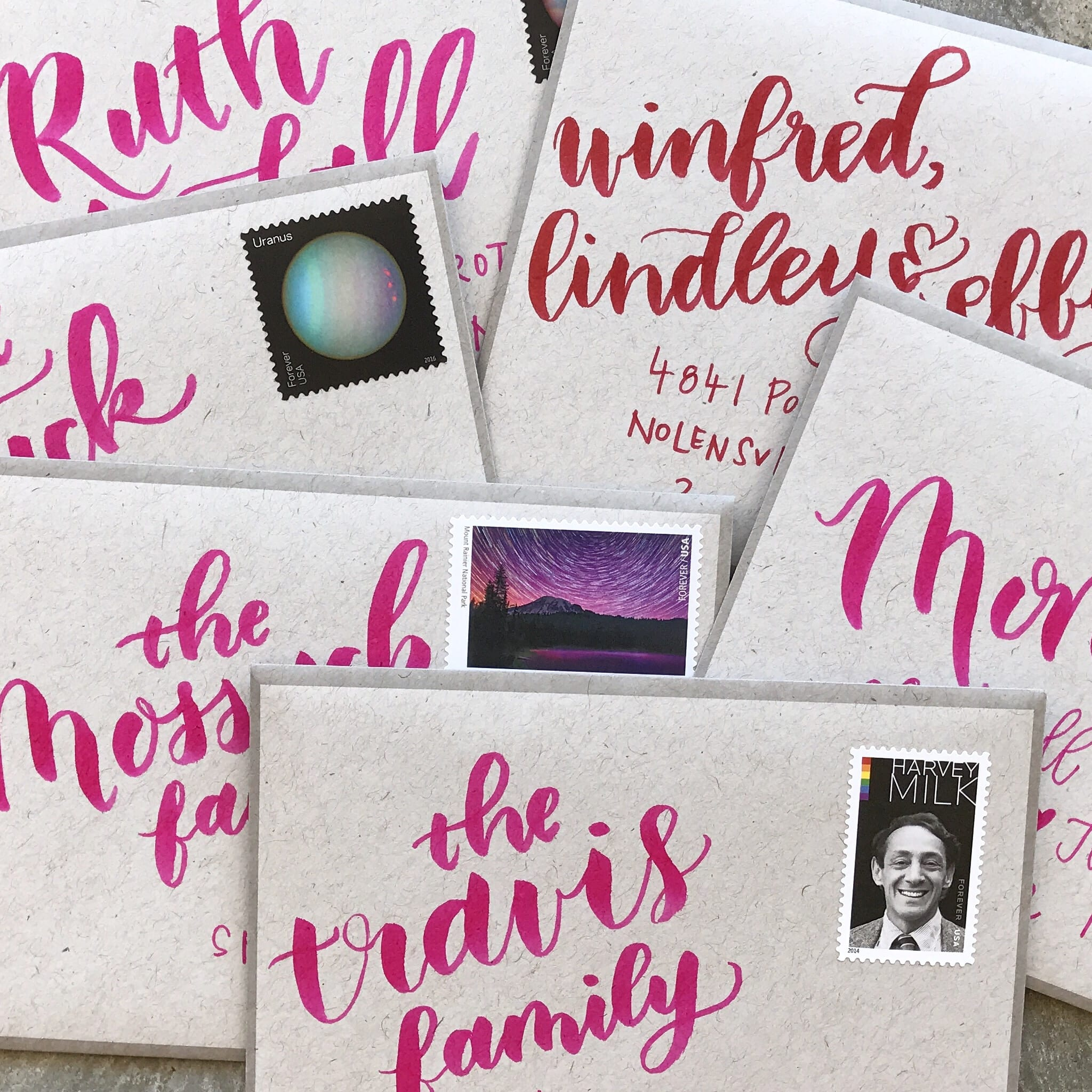 Hot pink brushed lettering on envelopes in a pile.