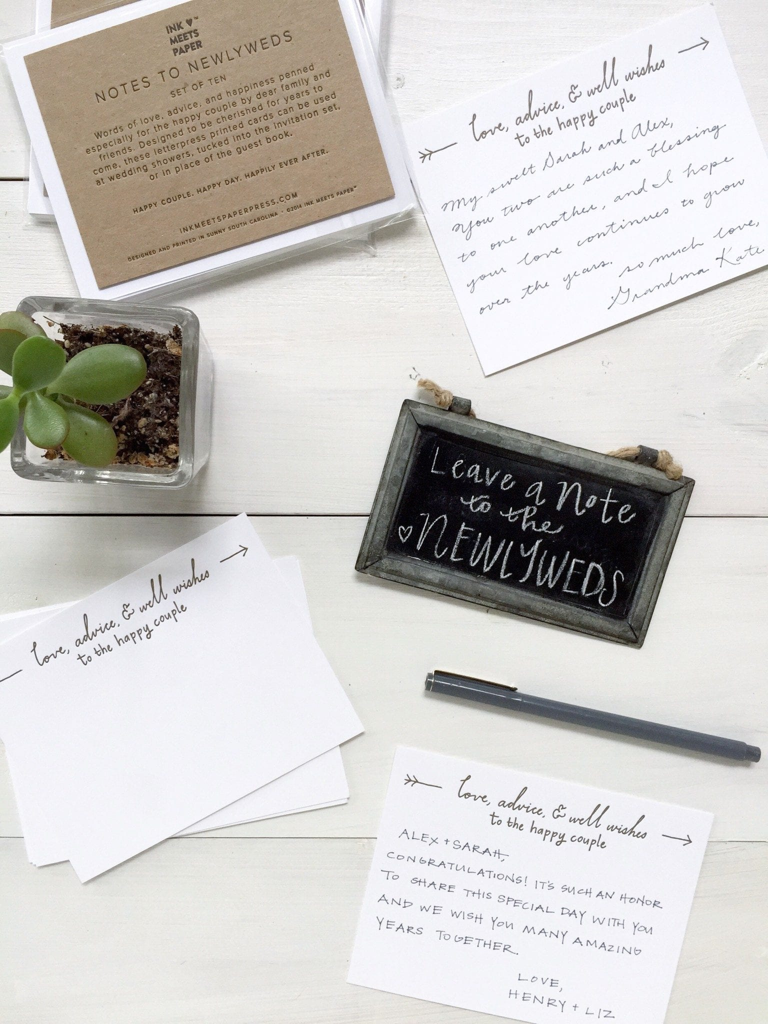 Adviced cards on a table filled out with small chalkboard message and jade plant.